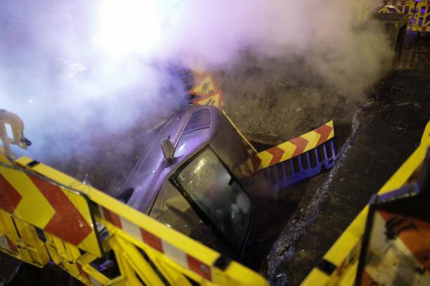 O masina a intrat complet intr-o groapa de pe o strada din Bucuresti din care iesea abur